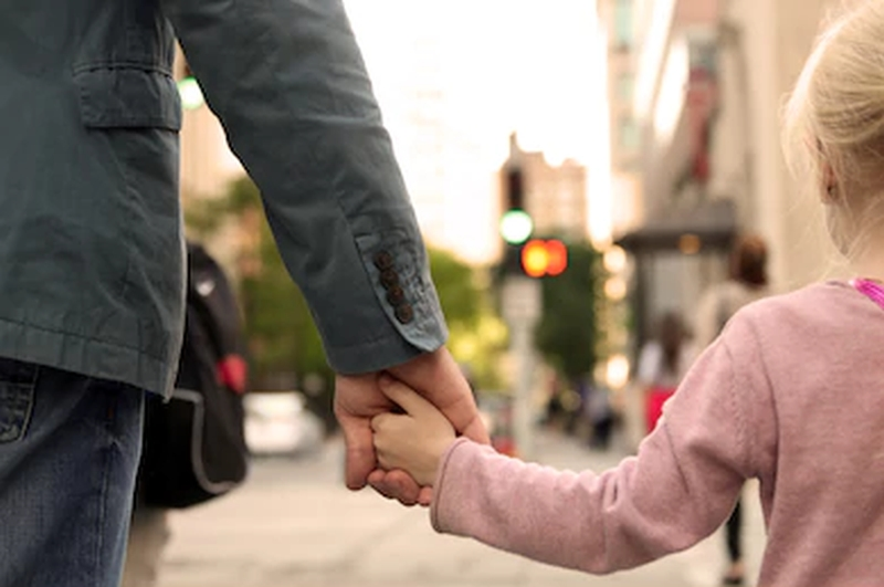 father-holding-child's-hand-crossing-street